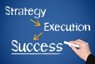 This image shows a hand writing on a blueboard with chalk three words connected by arrows: Strategy - Execution - Success (larger and underlined).